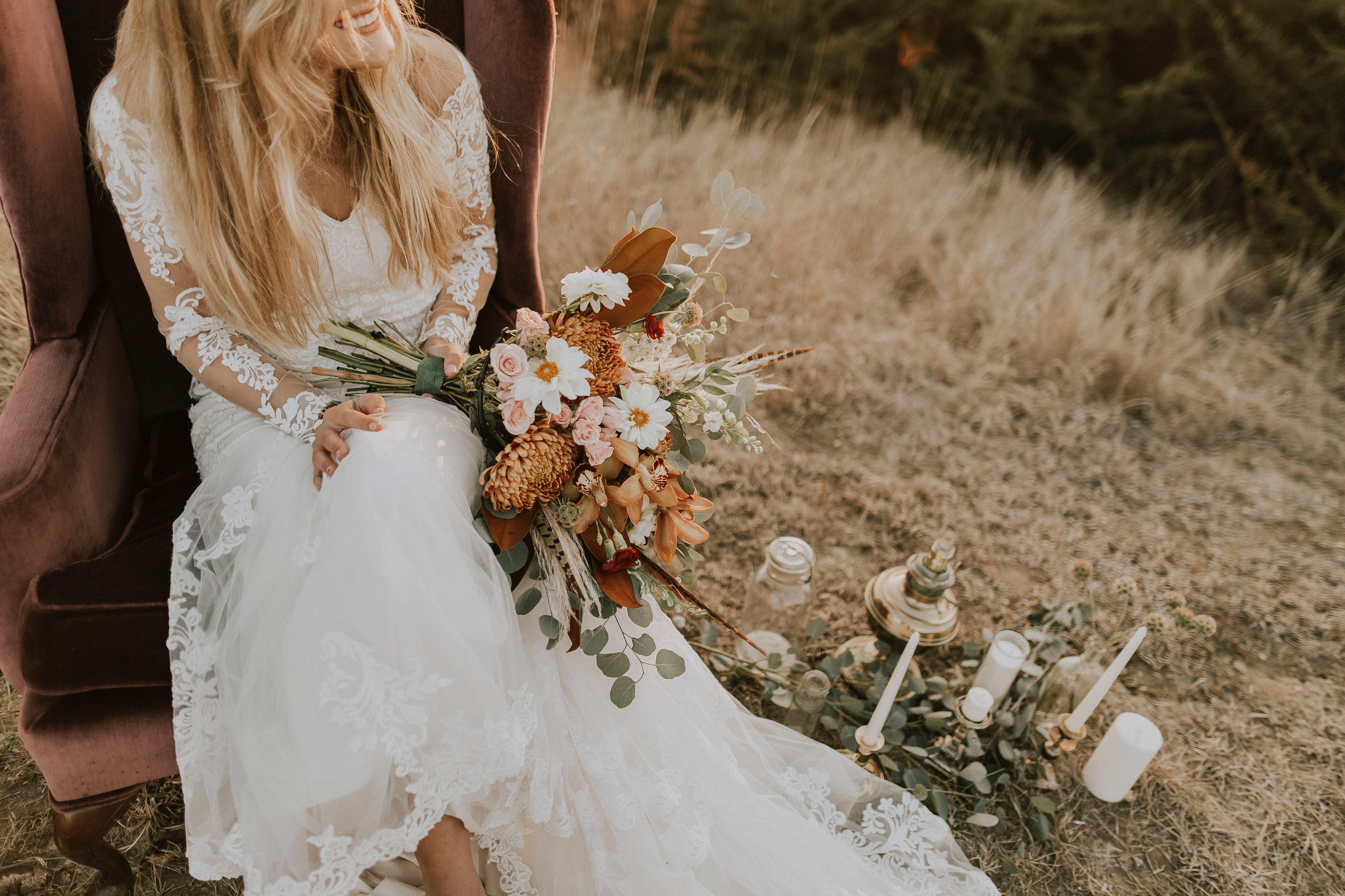 mariée assis tenant un bouquet de fleurs
